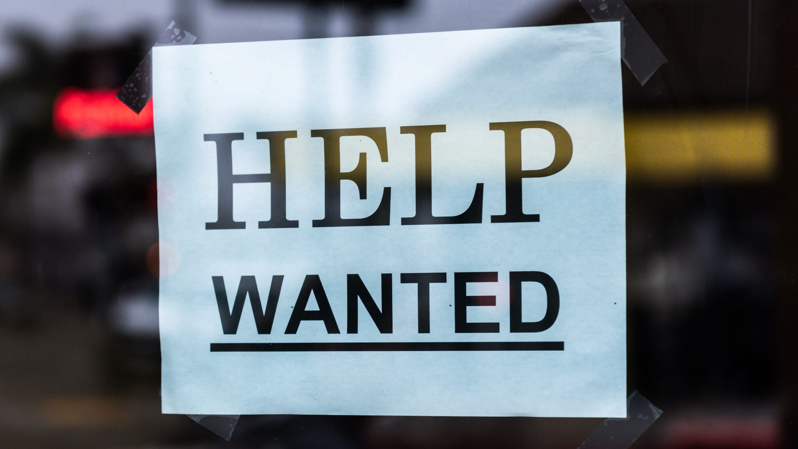help wanted sign taped on glass